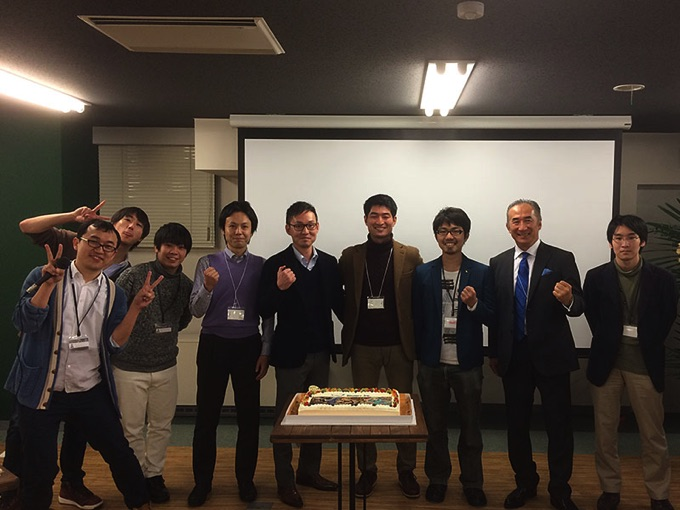 ケーキの前で上原社長と、坪井社長、INDETAILゲーム運営事業部のみなさんで記念写真!