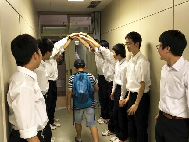 琴似工業高校の情報技術科のスタッフがアーチを作って参加した小学生をお見送り中
